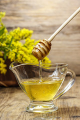 Bowl of honey on wooden background