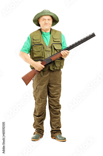 Full length portrait of male hunter holding a rifle