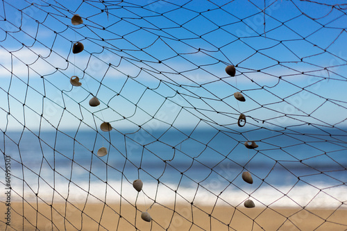 fishing net on beach, sea and sky at background