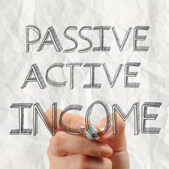 close up of hand drawing passive or acctive income as concept