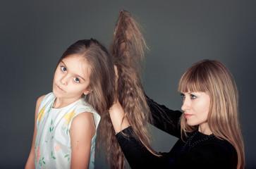 Mother combing her daughter