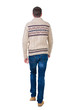 Back view of going  handsome man in jeans and warm sweater.