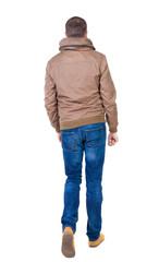 Back view of going  handsome man in brown wind breaker