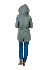back view of walking  woman in winter jacket with hood.