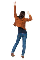 Back view of  joyful woman celebrating victory hands up
