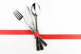 Fork, knife and spoon tied up with red ribbon