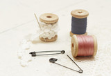 Sewing background. Spool of thread, lace and pins