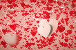 Two white hearts on a background full of red hearts with shallow