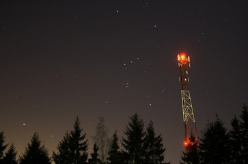 Telecommunication tower on night sky with stars