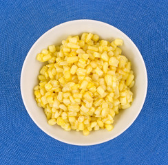 Buttered small shoepeg corn in a bowl on a blue placemat