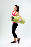 Young sport woman with yoga mat on gray background