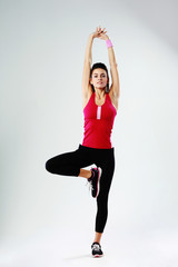 Young sport woman exercising on one leg on gray background