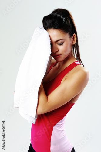 Young tired sport woman with towel on gray background