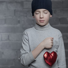 Serious boy holding heart, studio