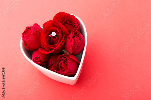 Red rose and diamond ring inside heart shape bowl over the red b