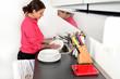 Ragazza in cucina che lava i piatti nel lavello