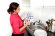 Ragazza in cucina che asciuga i piatti