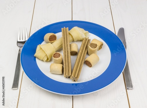 Dog biscuits and bone on a dinner plate at the table