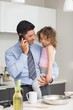 Well dressed father with daughter preparing food while on call