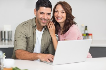 Portrait of a happy couple using laptop in kitchen