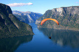 Paraglider flies through the Norwegian fjord