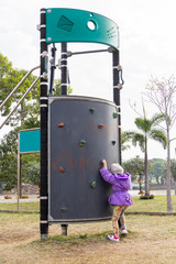 a girl climbing up the climbing wall at the playground,thailand