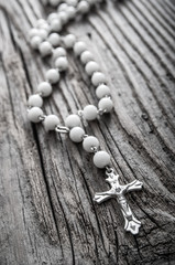 Rosary on old wooden background
