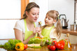 mother feeding kid vegetables in kitchen