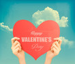 Two hands holding red heart Valentine's day retro background. Ve