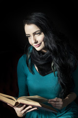 Beautiful Woman Reading a Book on Black Background