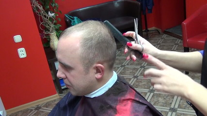 Barber cutting hair with scissors comb
