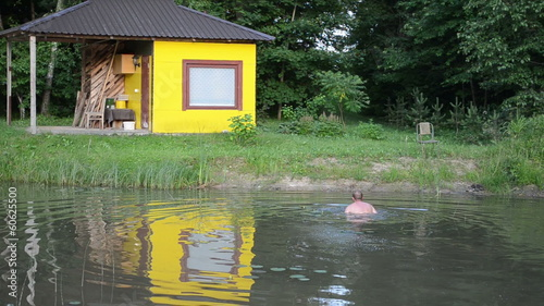 yellow bathhouse to the village pond shore man climbs to shore