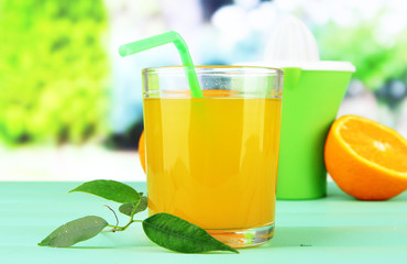 Citrus press, glass of juice and ripe orange