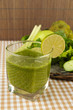 Glass of green vegetable juice and vegetables