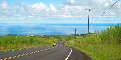 Empty road in Hawaiian countryside with car and ocean in backgro