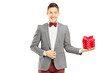 Fancy dressed young man holding a present