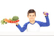 Young boy holding plate full of vegetables and dumbbell