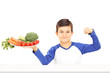 Young boy holding plate full of vegetables and showing muscle