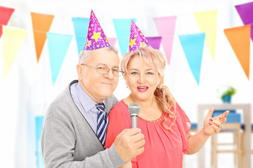 Mature couple with party hats singing at a celebration