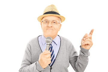 Senior gentleman holding microphone and pointing up with finger