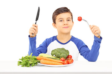 Young boy eating vegetables seated at table