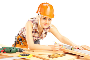 Young female carpenter working and looking at camera
