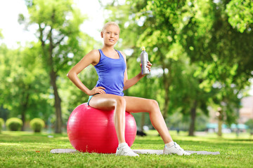 Young female athlete sitting on pilates ball holding a bottle