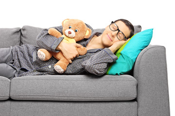 Young guy sleeping on sofa holding a teddy bear