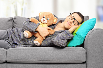 Young man holding teddy bear and taking a nap on couch