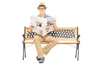 Young man seated on a wooden bench holding newspaper