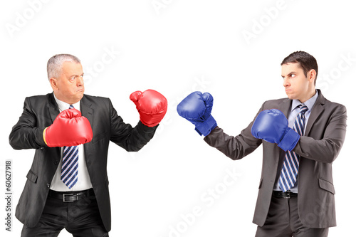 Mature businessman with boxing gloves ready to fight his coworke