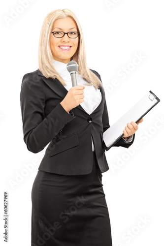 Young female presenter holding microphone and clipboard