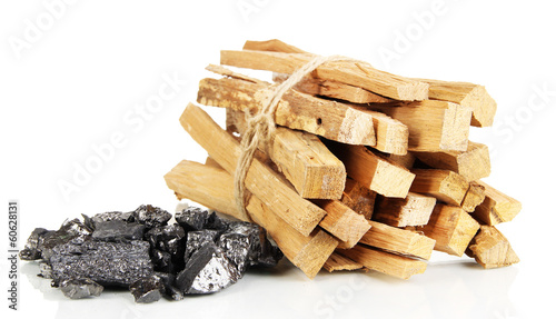 Stack of firewood and heap of coal isolated on white