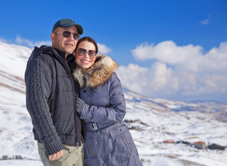 Loving couple in snowy mountains